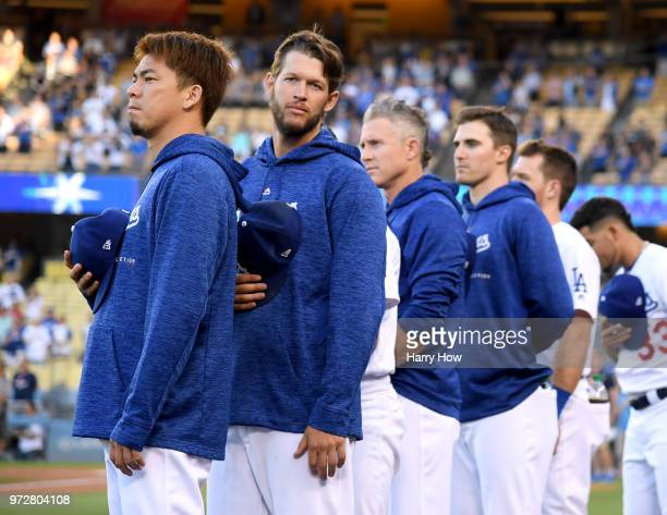 Kenta Maeda and Clayton Kershaw of the Los Angeles Dodgers line up for the National Anthem before the game against the Texas Rangers at Dodger...