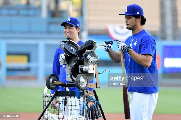 Kenta Maeda and Yu Darvish of the Los Angeles Dodgers talk on the field ahead of the World Series at Dodger Stadium on October 23 2017 in Los Angeles...