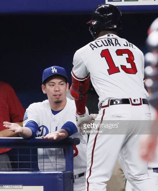 Kenta Maeda congratulates Ronald Acuna Jr after the latter hit a solo home run in the eighth inning of Game 6 of the MLBJapan AllStar Series in...