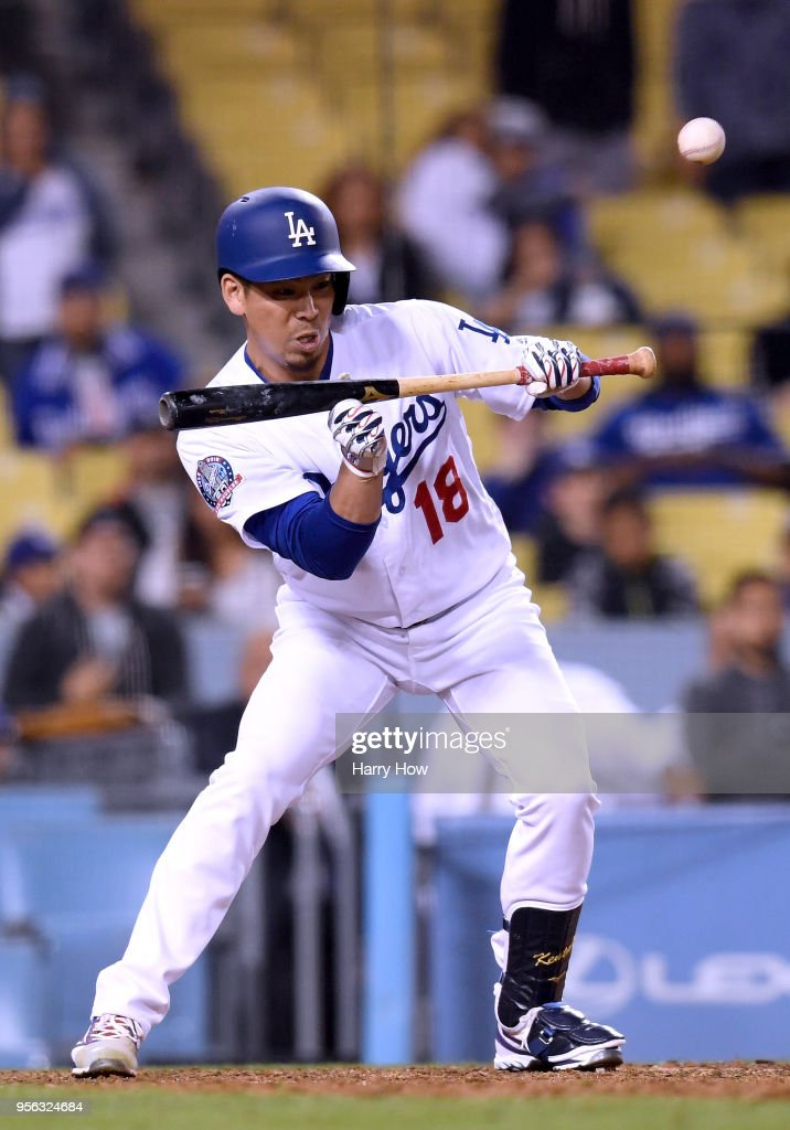 Kenta Maeda #18 of the Los Angeles Dodgers bunts during the 12th inning against the Arizona Diamondbacks at Dodger Stadium on May 8, 2018 in Los Angeles, California.