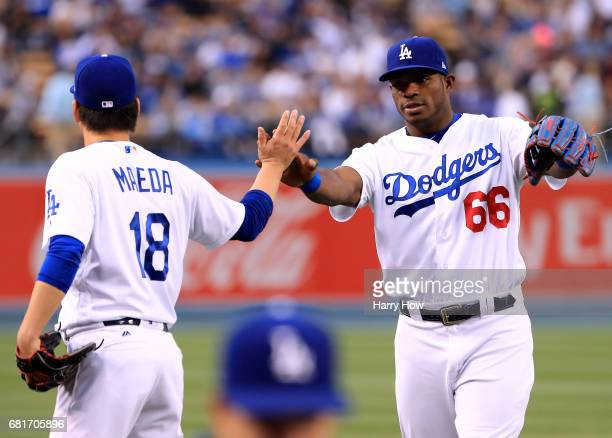 Kenta Maeda of the Los Angeles Dodgers celebrates a catch with Yasiel Puig at the end of the top of the first inning against the Pittsburgh Pirates...