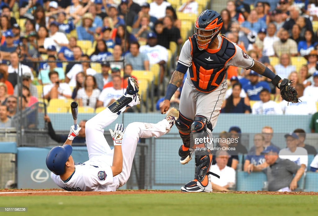 Kenta Maeda #18 of the Los Angeles Dodgers falls on the ground after a swinging strike as Martin Maldonado #15 of the Houston Astros throws out Austin Barnes #15 of the Los Angeles Dodgers as he attempted to steal second base in the third inning at Dodger Stadium on August 4, 2018 in Los Angeles, California.