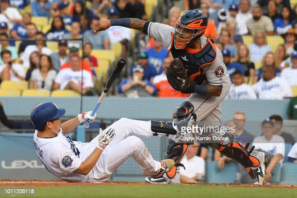Kenta Maeda of the Los Angeles Dodgers falls on the ground after a swinging strike as Martin Maldonado of the Houston Astros throws out Austin Barnes...