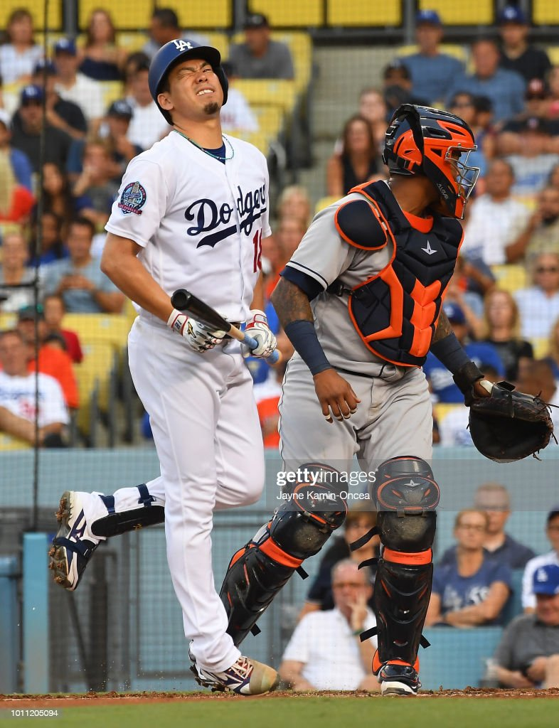 Kenta Maeda #18 of the Los Angeles Dodgers grimaces after missing a bunt whle at bat in the third inning at Dodger Stadium on August 4, 2018 in Los Angeles, California.