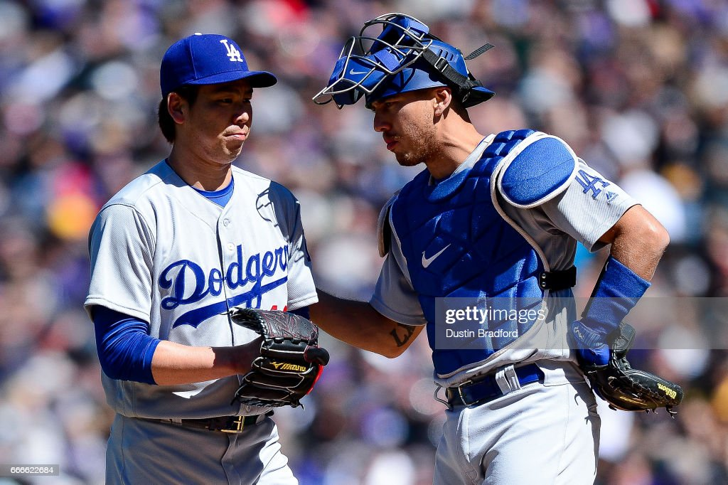 Kenta Maeda #18 of the Los Angeles Dodgers has a word with catcher Austin Barnes #15 second inning of a game against the Colorado Rockies at Coors Field on April 9, 2017 in Denver, Colorado.