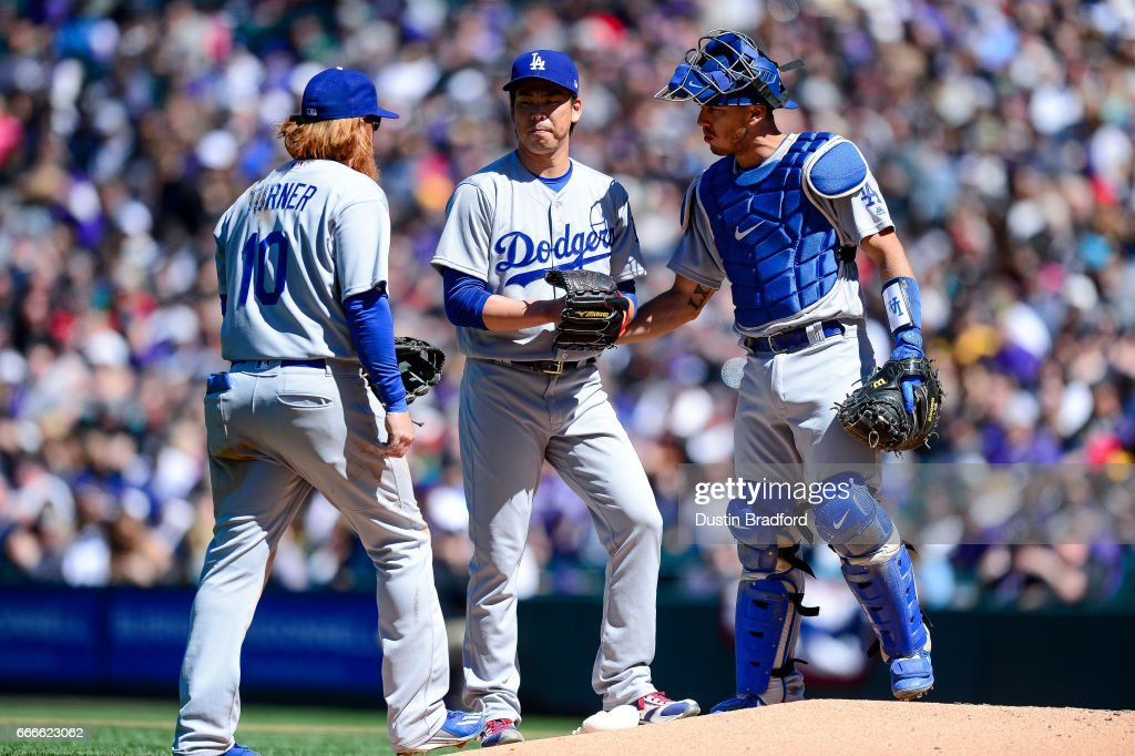 Kenta Maeda #18 of the Los Angeles Dodgers has a word with catcher Austin Barnes #15 and Justin Turner #10 in the second inning of a game against the Colorado Rockies at Coors Field on April 9, 2017 in Denver, Colorado.