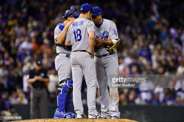 Kenta Maeda of the Los Angeles Dodgers has a word with Manny Machado and Austin Barnes as he pitches in a ninth inning appearance with a runner on...