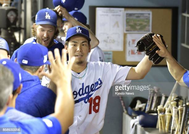 Kenta Maeda of the Los Angeles Dodgers high fives teammates in the dugout at Dodger Stadium in Los Angeles on Oct 7 after pitching against the...