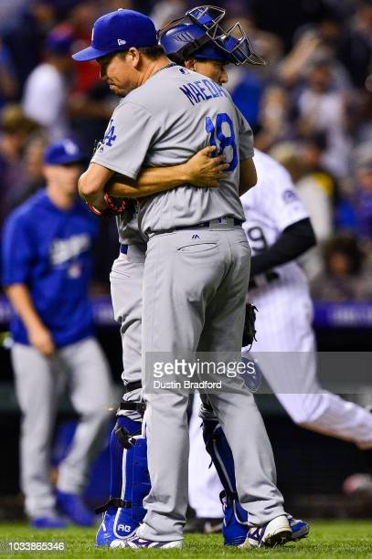 Kenta Maeda of the Los Angeles Dodgers is congratulated by Austin Barnes after a save from a ninth inning appearance with a runner on and one out...