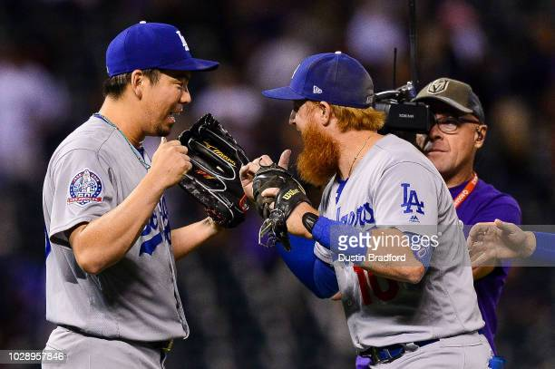 Kenta Maeda of the Los Angeles Dodgers is congratulated by Justin Turner after a save from a ninth inning appearance with a runner on and one out...