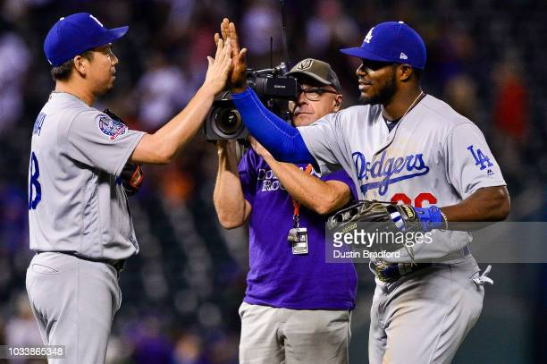 Kenta Maeda of the Los Angeles Dodgers is congratulated by Yasiel Puig after getting the save with a runner on and one out against the Colorado...