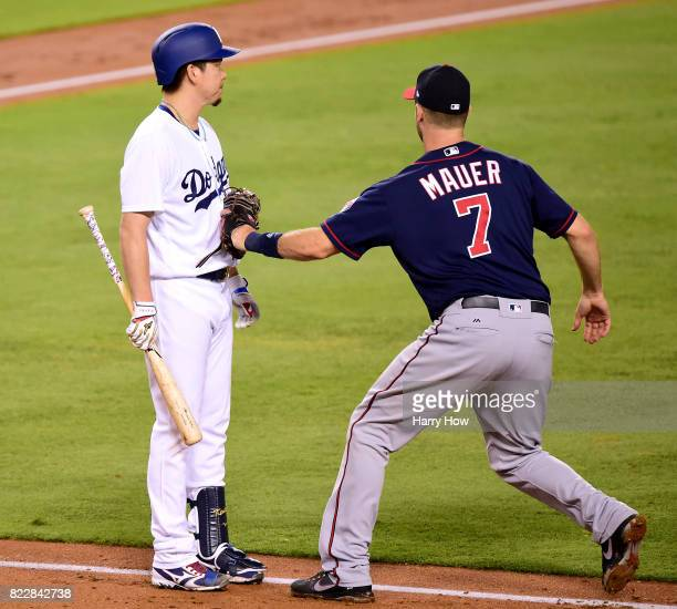 Kenta Maeda of the Los Angeles Dodgers is tagged out by Joe Mauer of the Minnesota Twins on a sacrifice bunt during the third inning at Dodger...