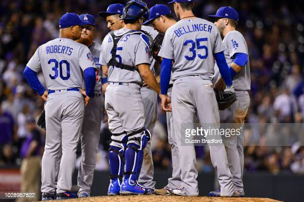 Kenta Maeda of the Los Angeles Dodgers talks to manager Dave Roberts and teammates as he takes the field for a ninth inning appearance with a runner...