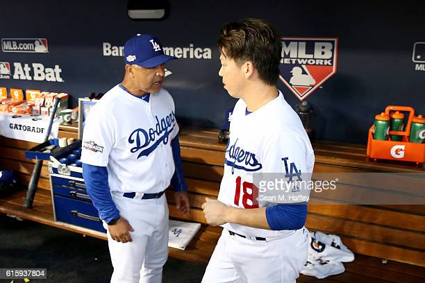 Kenta Maeda of the Los Angeles Dodgers talks with manager Dave Roberts in the dugout against the Chicago Cubs in game five of the National League...