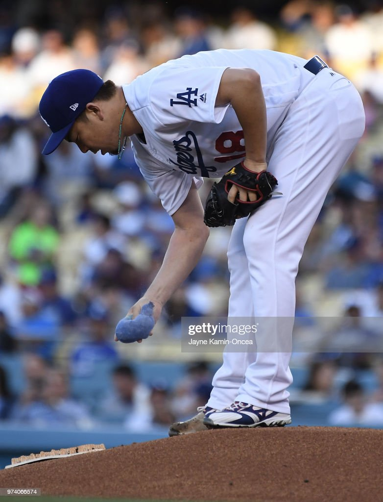 Kenta Maeda #18 of the Los Angeles Dodgers uses a rosin bag to dry his hand before throwing the first pitch of the game against the Texas Rangers at Dodger Stadium on June 13, 2018 in Los Angeles, California.