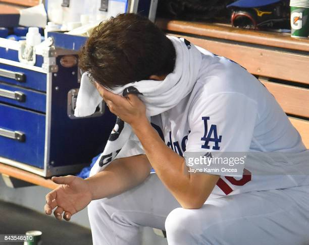 Kenta Maeda of the Los Angeles Dodgers wipes his face as he sits in the dugout after the fifth inning of the game against the Arizona Diamondbacks at...