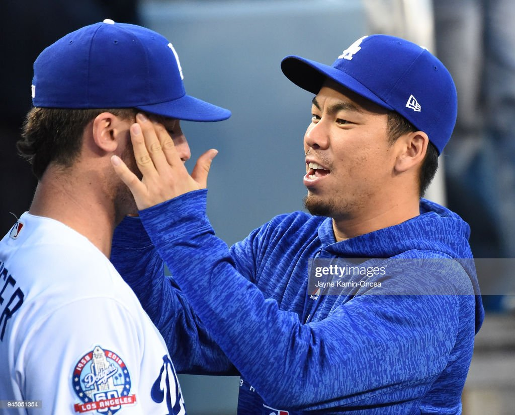 Kenta Maeda #18 rubs on the face of Cody Bellinger #35 of the Los Angeles Dodgers in the dugout before the start of the game against the Oakland Athletics at Dodger Stadium on April 11, 2018 in Los Angeles, California.