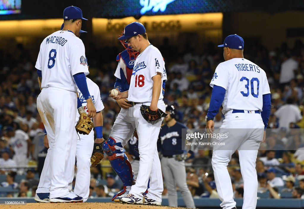Kenta Maeda #18 waits on the mound with Manny Machado #8 to be pulled from the fifth inning of the game by manager Dave Roberts #30 of the Los Angeles Dodgers against the Milwaukee Brewers at Dodger Stadium on July 30, 2018 in Los Angeles, California.