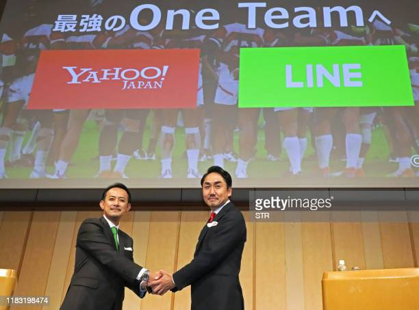 Kentaro Kawabe , CEO and president of Z Holdings and Takeshi Idezawa , CEO and president of LINE shake hands during a joint press conference in Tokyo...