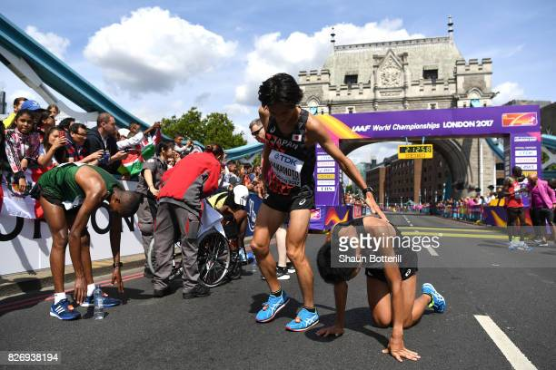 Kentaro Nakamoto of Japan and Hiroto Inoue of Japan react after crossing the finishline in the Men's Marathon during day three of the 16th IAAF World...