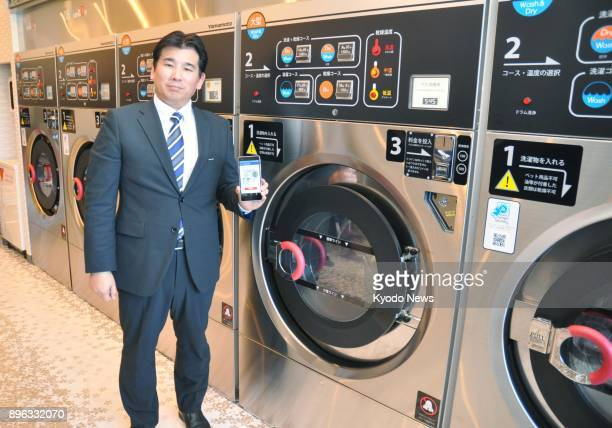 Kentaro Takanashi president of selfservice laundry operator Wash Plus shows how various functions on washing machines at his company's coin...