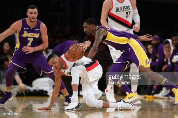 Kentavious CaldwellPope and Larry Nance Jr #7 of the Los Angeles Lakers defend against Evan Turner of the Portland Trail Blazers during the first...
