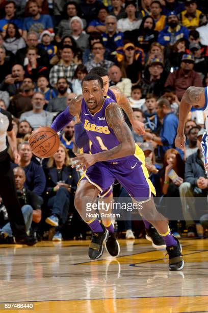 Kentavious CaldwellPope of the Los Angeles Lakers drives to the basket against the Golden State Warriors on December 22 2017 at ORACLE Arena in...