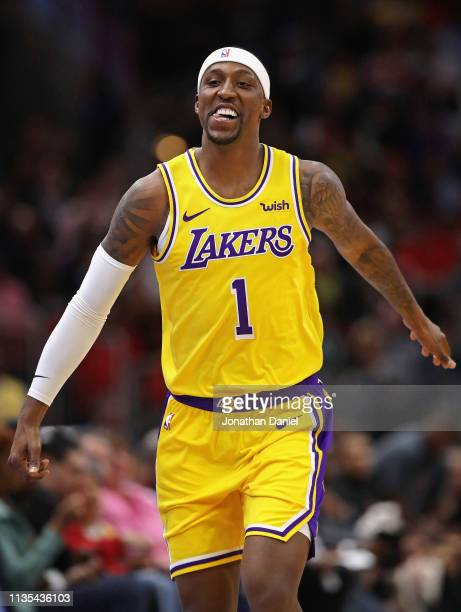 Kentavious CaldwellPope of the Los Angeles Lakers smiles as he leaves the court during a time out after hitting a three point shot against the...