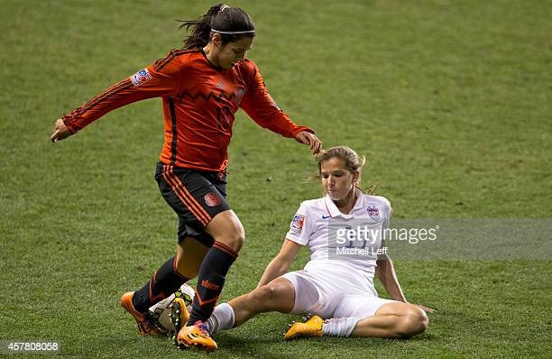 Kenti Robles of Mexico dribbles the ball and is stopped with a slide tackle by Lauren Holiday of the United States in the second half of the 2014...