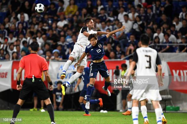 Kento Misao of Japan and Jonathan Moya of Costa Rica compete for the ball during the international friendly match between Japan and Costa Rica at...