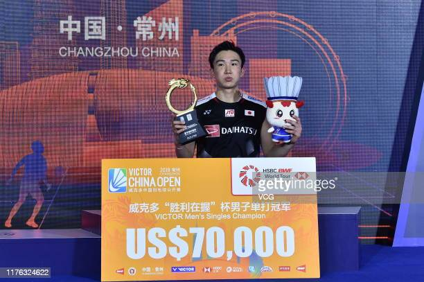 Kento Momota of Japan celebrates with the trophy on the podium after winning the Men's Singles final match against Anthony Sinisuka Ginting of...
