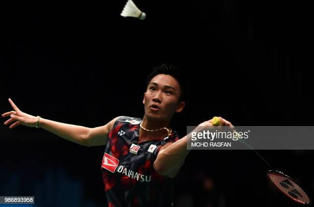 Kento Momota of Japan eyes a return against Chou Tien Chen of Taiwan during their men's singles quarterfinal match at the Malaysia Open Badminton...
