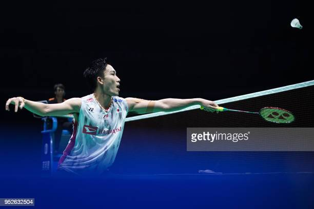 Kento Momota of Japan hits a return against Chen Long of China during their men's singles final match at the 2018 Badminton Asia Championships in...