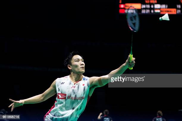 Kento Momota of Japan hits a return against Chou Tien Chen of Taiwan during their men's singles quarterfinals match at the 2018 Badminton Asia...