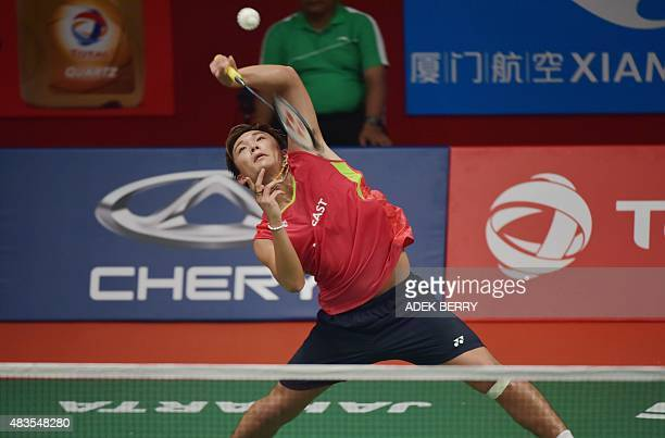 Kento Momota of Japan hits a return against Dieter Domke of Germany during their men's singles qualifying match at the 2015 World Championships...