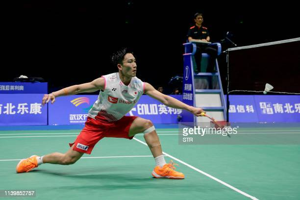 Kento Momota of Japan hits a return against Shi Yuqi of China during their men's singles final match at the 2019 Badminton Asia Championships in...