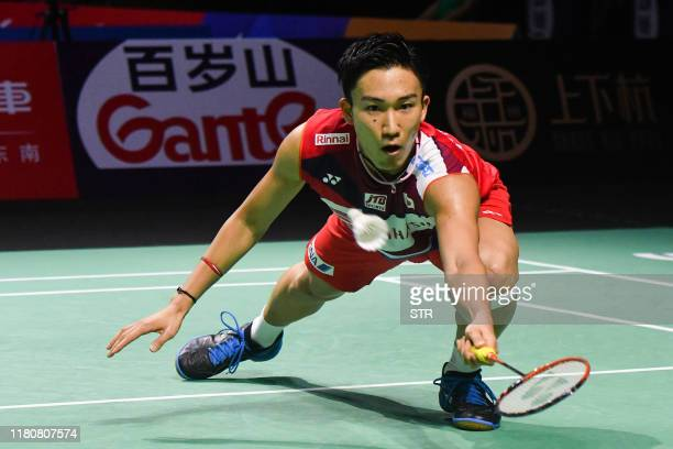 Kento Momota of Japan hits a return against Viktor Axelsen of Denmark during their men's singles quarterfinal match at the Fuzhou China Open...