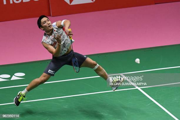 Kento Momota of Japan hits a return against Viktor Axelsen of Denmark during their men's singles semifinals match at the Thomas and Uber Cup...