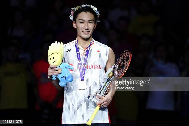 Kento Momota of Japan poses with her medal on the podium after defeating Shi Yuqi of China in the men's singles final on day 7 of Total BWF World...