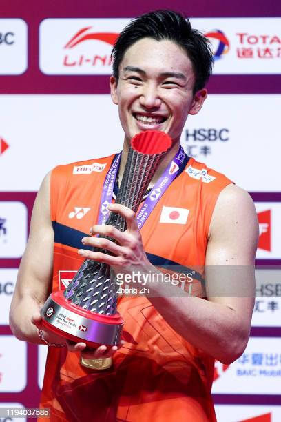 Kento Momota of Japan reacts with trophy during award ceremony after winning the men's singles final match against Anthony Sinisuka Ginting of...