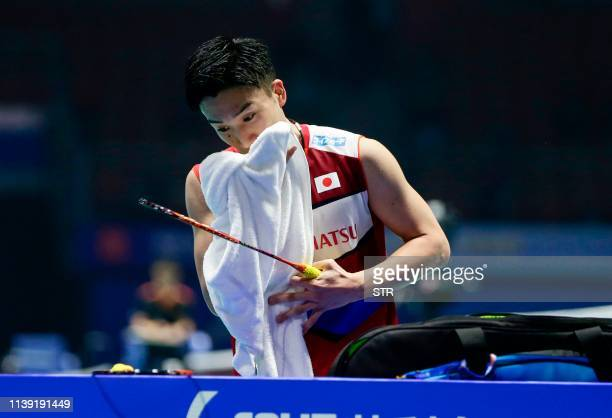 Kento Momota of Japan uses a towel during his men's singles second round match against Lee Cheuk Yiu of Hong Kong at the 2019 Badminton Asia...