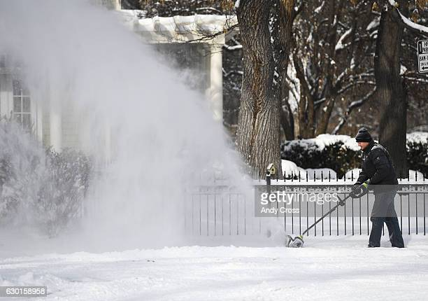 Kenton Epard uses a battery powered snow broom to clear his sidewalk near Fillmore St and Warren Ave December 17 2016