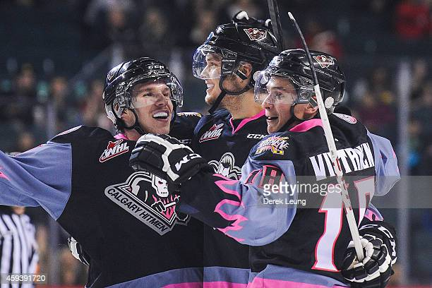 Kenton Helgesen of the Calgary Hitmen celebrates his goal against the Moose Jaw Warriors along with his teammates Keegan Kanzig and Jake Virtanen...