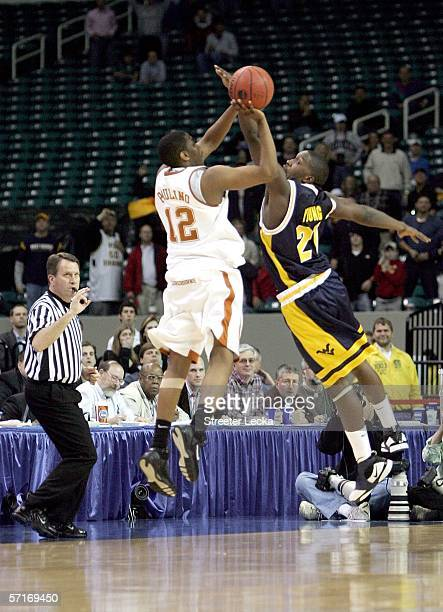 Kenton Paulino of the Texas Longhorns shoots the game winning three pointer over Frank Young of the West Virginia Mountaineers during third round...