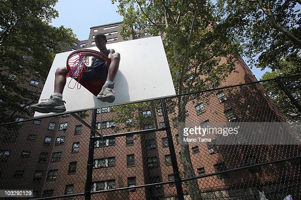 Kentrelle Burrell sits on a basketball hoop near to where a street baptism was conducted by the United House of Prayer for All People in Harlem on...