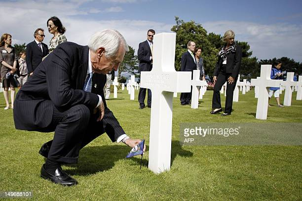 Kentucky Governor Steve Beshear puts a Kentucky model flag next to a cross in a memory of a dead WWII soldier from Kentucky at the American Military...