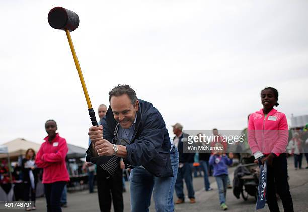 Kentucky Republican senatorial candidate Matt Bevin swings a mallet while ringing the bell on the 'High Striker' game at the Fountain Run BBQ...