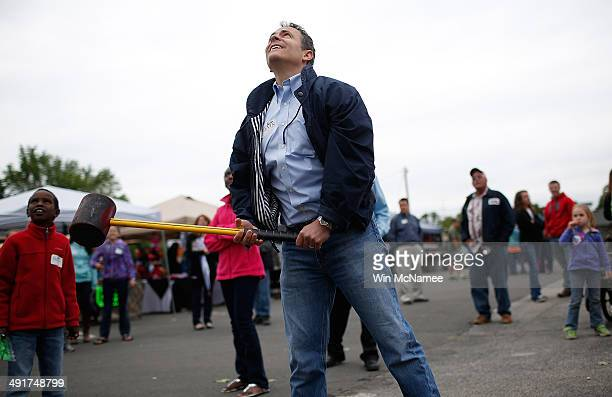 Kentucky Republican senatorial candidate Matt Bevin watches as he rings the bell on the 'High Striker' game at the Fountain Run BBQ Festival while...