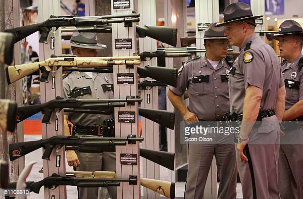 Kentucky State Police officers look over the Benelli shotgun display prior to the opening of the exhibit hall for the National Rifle Association of...