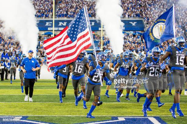 Kentucky wide receiver Bryan Berezowitz carries the American flag onto the field before a regular season college football game between the Florida...